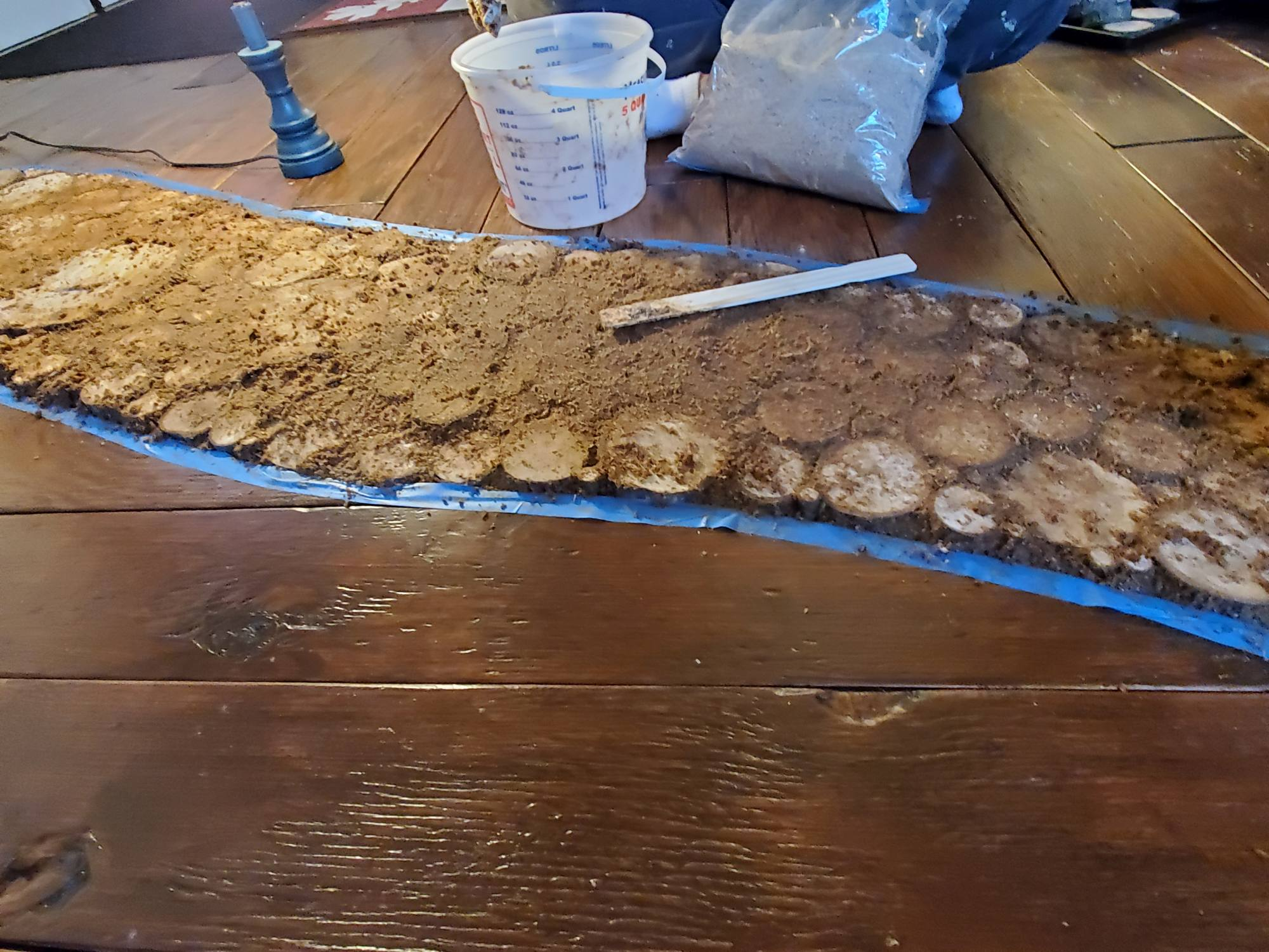 Installing An End Grain Flooring Inlay - The wood slices are in place and the sawdust grout is being applied